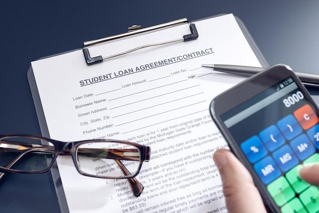 Solicitud de préstamo estudiantil en blanco con calculadora de teléfono, bolígrafo y gafas en la mesa sobre fondo negro