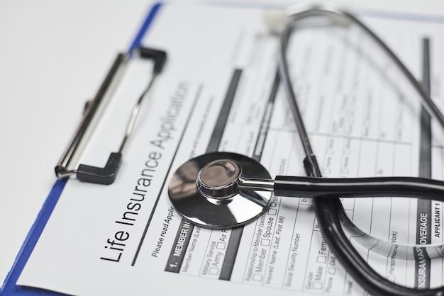 Solicitud de seguro de vida en blanco y un estetoscopio