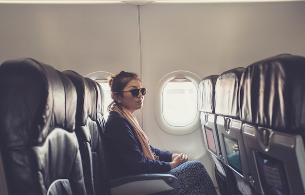 Solitaria mujer asiática sentada al lado de la ventana del avión uso para viajar tema