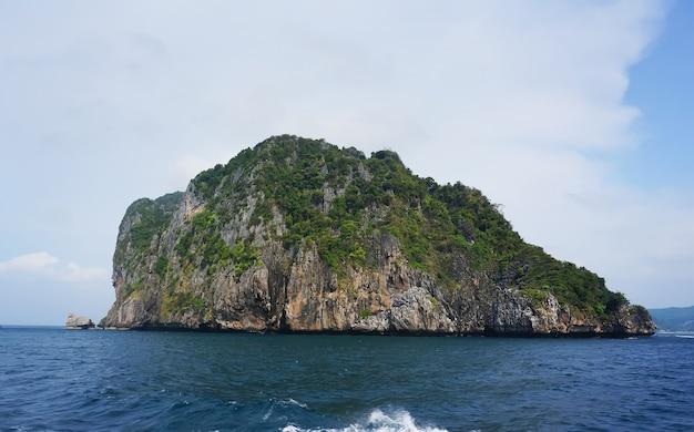 Solitaria una pequeña isla rocosa en medio del océano .. isla mar arena sol playa naturaleza destino fondo de pantalla y fondo para diseño en krabi y phuket en tailandia