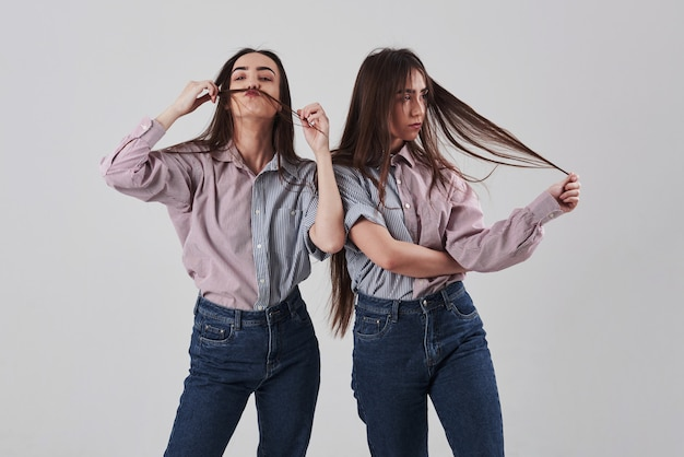 Solo bromeando. dos hermanas gemelas de pie y posando en el estudio con fondo blanco.