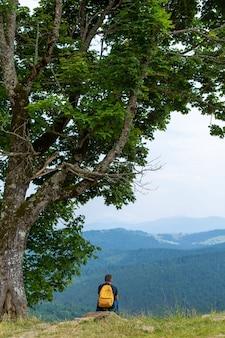 Solo chico sentado en el acantilado y disfrutar del pacífico paisaje de montañas verdes. tranquilidad y relax.