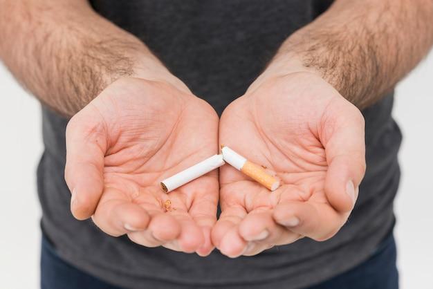 Un solo cigarrillo roto en la mano del hombre.