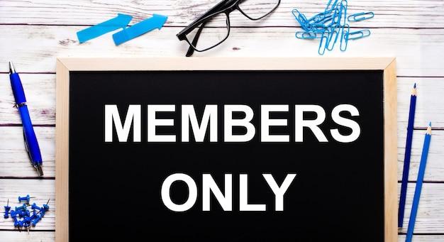 Solo miembros escrito en una pizarra negra junto a clips azules, lápices y un bolígrafo