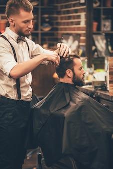 Solo un poco de aquí. joven barbudo cortarse el pelo por peluquero