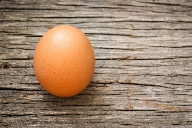 Un solo sencillo de huevo en mesa de madera con espacio de copia