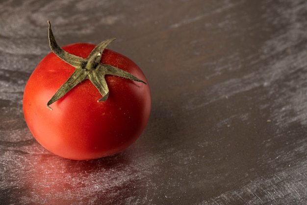 Un solo tomate rojo sobre un fondo metálico plateado.