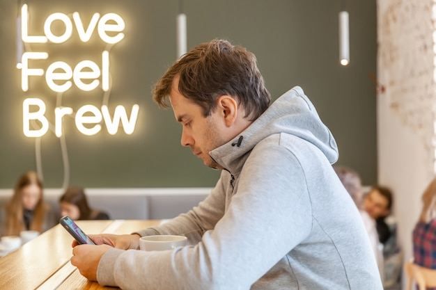 Solo triste hombre infeliz sentado en la cafetería con teléfono inteligente y una taza de capuchino