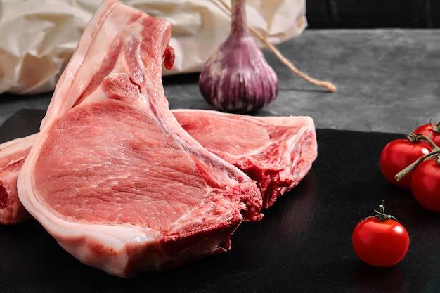 Solomillo de cerdo con hueso dos trozos de carne de cerdo en una placa de pizarra sobre una mesa gris