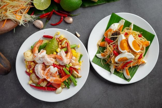 Som tum con maíz y camarones, servido con fideos de arroz y ensalada verde. decorado con ingredientes de comida tailandesa.