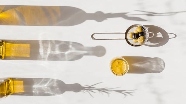 Sombra de la botella de aceite con aceitunas en el colador de té sobre fondo blanco