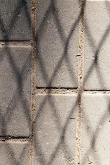 Sombra de la cuadrícula en la carretera de baldosas de hormigón, primer plano de la foto en la ciudad