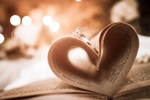 Sombra de forma abstracta de corazón de dos anillos de boda en un libro