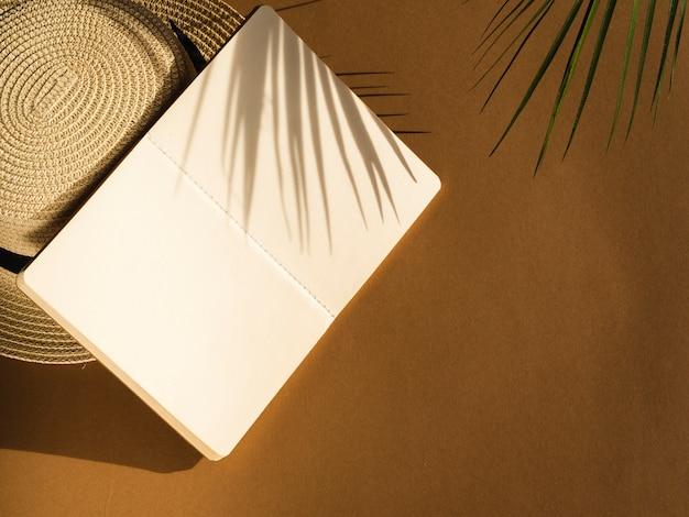 Sombra de hojas sobre un fondo beige y un cuaderno y un sombrero