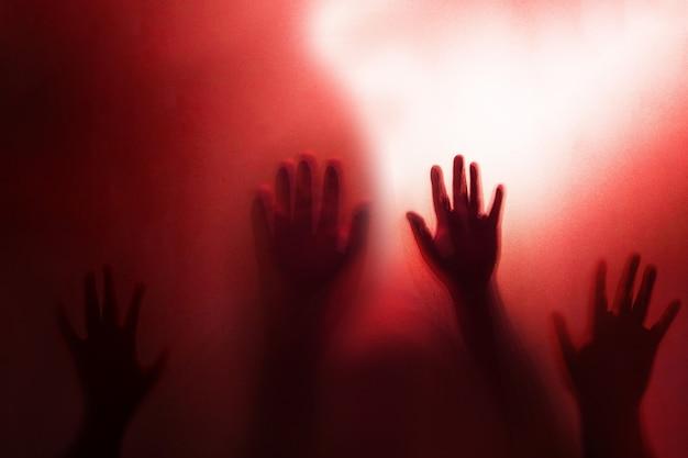 Sombra de la mano fantasma detrás del vidrio esmerilado