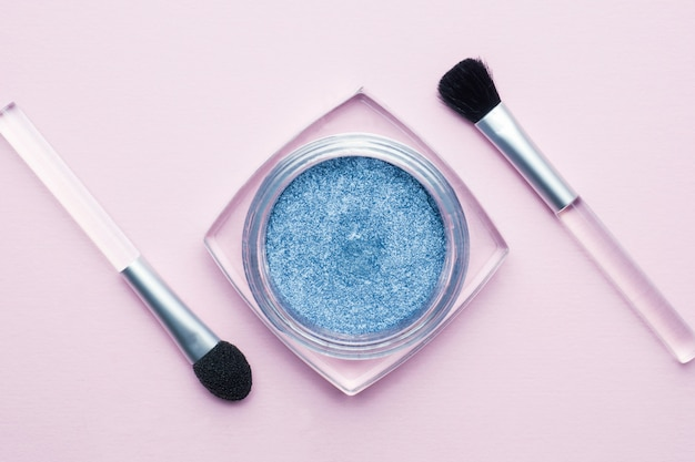 Sombra de ojos azul con borlas sobre fondo rosa pastel. concepto de belleza y maquillaje.