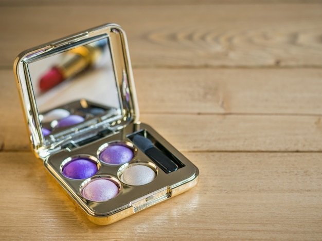Sombra de ojos y se refleja en el lápiz labial espejo en una mesa de madera vintage.