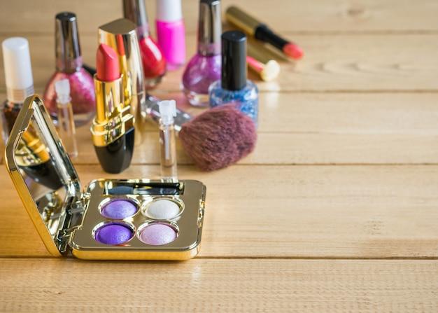 Sombra de ojos y se refleja en el lápiz labial espejo en una mesa rústica vintage.
