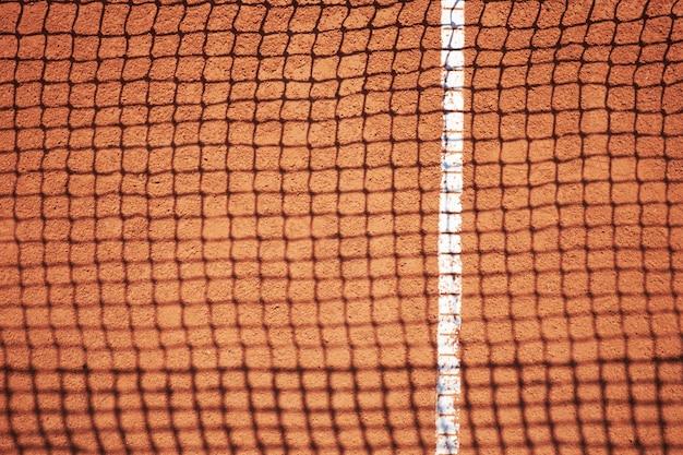 Sombra de red de tenis en campo de arena roja