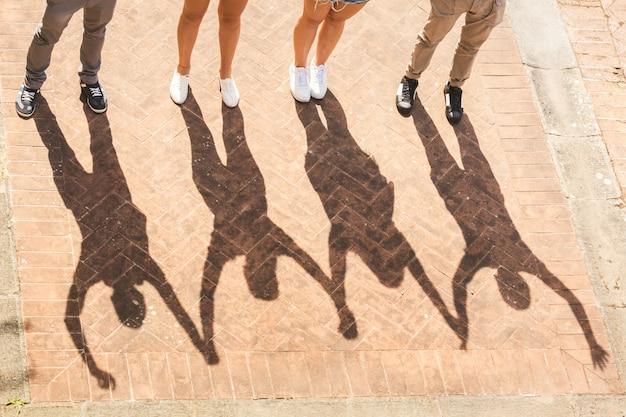 Sombras de amigos sosteniendo y levantando las manos juntas.