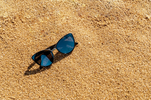 Sombras en la arena amarilla en la playa. concepto de vacaciones de verano. protección de las gafas contra la radiación uv.