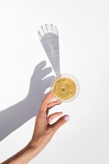 Sombras de moda de la copa de champán con la mano. vista superior