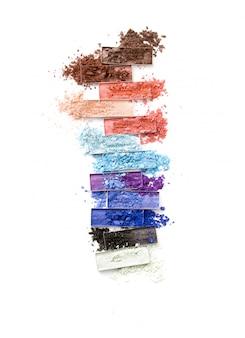 Sombras de ojos trituradas multicolores con pincel aislado en blanco