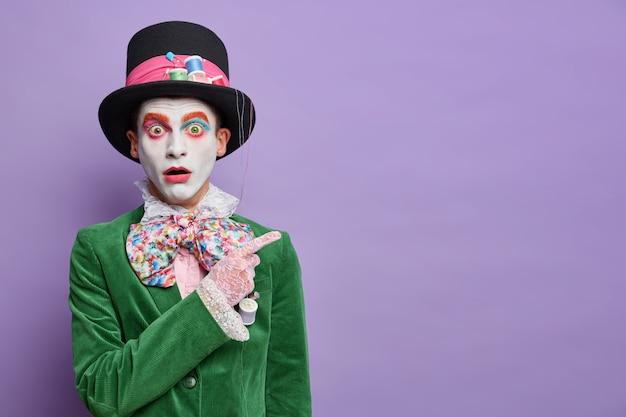 Sombrerero avergonzado sorprendido en la fiesta de disfraces indica en la esquina superior derecha aturdido por algo horrible aislado sobre la pared púrpura muestra un espacio vacío para su información