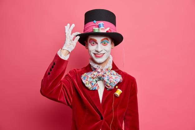 Sombrerero loco positivo mantiene la mano en el sombrero sonríe felizmente participa en vestidos de carnaval para poses de fiesta de halloween contra la pared rosada