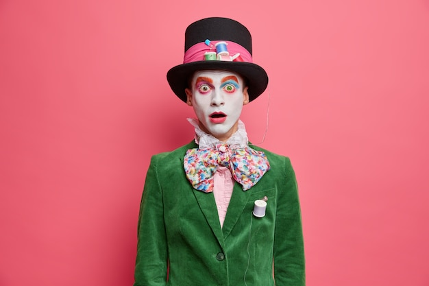 Sombrerero sorprendido y avergonzado mira a la cámara con ojos saltones vestido con una chaqueta verde y un sombrero grande con maquillaje colorido que participa en la actuación aislada sobre una pared rosada