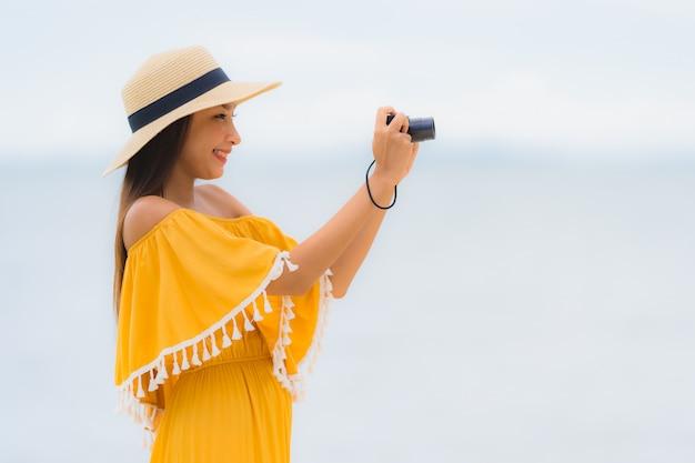 El sombrero asiático hermoso del desgaste de mujer del retrato con ocio feliz de la sonrisa adentro toma una foto en la playa y el mar en vacaciones del día de fiesta