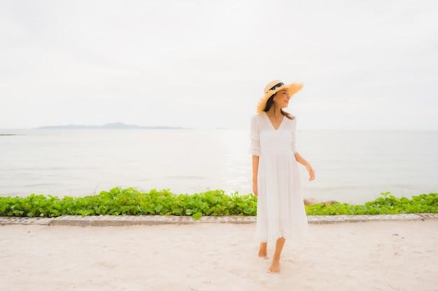 Sombrero asiático hermoso del desgaste de mujer del retrato con ocio feliz de la sonrisa en la playa y el mar en vacaciones del día de fiesta