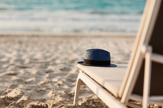 Sombrero azul se encuentra en una tumbona en la playa