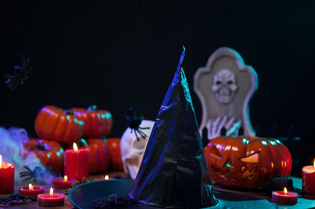 Sombrero de bruja aterrador sentado en una mesa de madera celebrando halloween. calabazas naranjas para halloween.