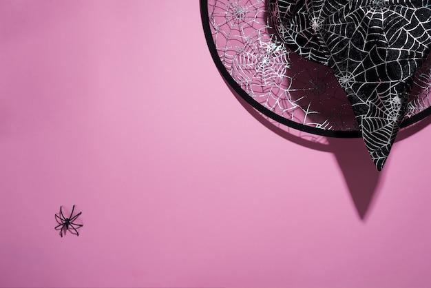 Sombrero de bruja negro con un patrón de telarañas y araña sobre fondo rosa