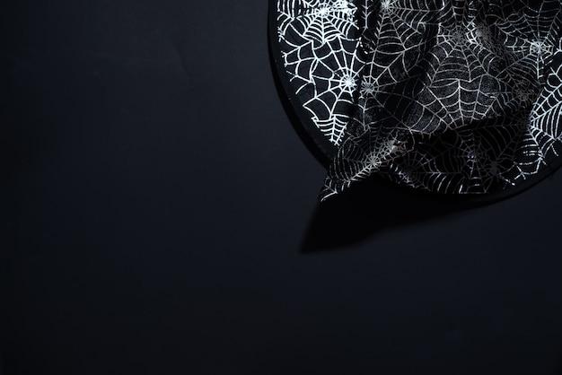 Sombrero de bruja negro con un patrón de telarañas sobre fondo negro