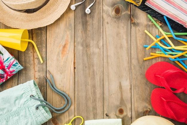 Sombrero cerca de auriculares y chanclas con taza y pajitas.