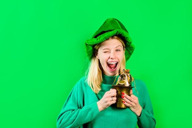 Sombrero de copa verde chica rubia en traje de duende sostiene una bolsa con una bolsa de duende dorada con verde dorado