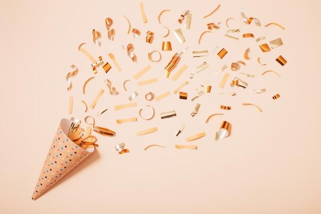 Sombrero de cumpleaños con confeti sobre papel