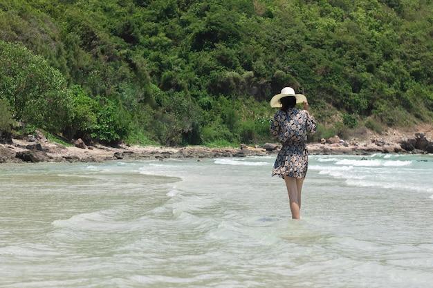 Sombrero del desgaste de mujer joven en una falda corta que camina en el océano. la muchacha y el mar en namsai varan chonburi, tailandia.
