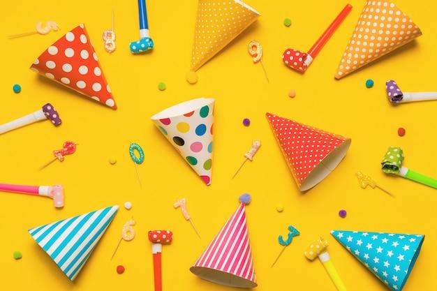 Sombrero de fiesta, velas, confitería, sopladores de fiesta sobre fondo amarillo con vista superior alta.