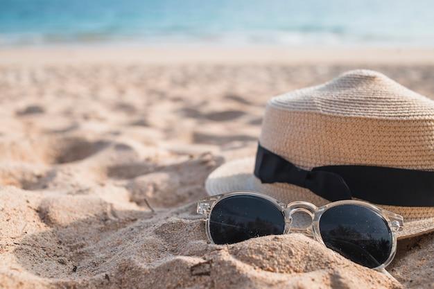 Sombrero con gafas de sol en la arena