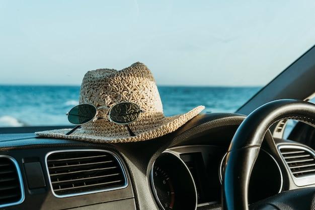 Sombrero y gafas de sol a bordo del coche.
