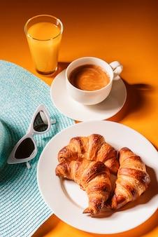 Sombrero, gafas de sol croissant con una taza de café y un vaso de jugo de naranja sobre una mesa amarilla al sol