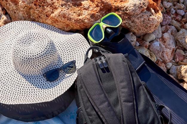 Sombrero, gafas de sol, mochila y aletas con máscara en la costa de piedra.