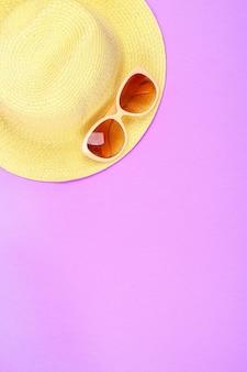 Sombrero, gafas de sol en rosa pastel, fondo púrpura.