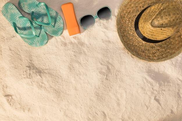 Sombrero gafas de sol sandalias azules y protector solar sobre arena.