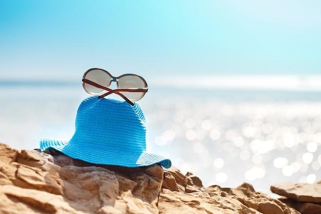 Sombrero y gafas de sol sobre la roca, mar claro. concepto de vacaciones de viaje.