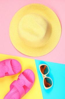 Sombrero, gafas de sol y zapatillas sobre un fondo pastel de tres colores.