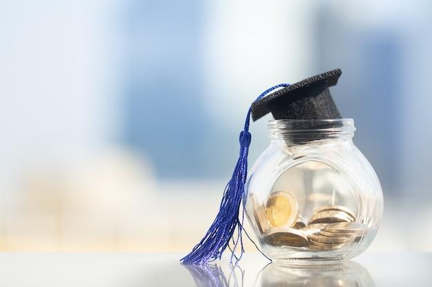 El sombrero de la graduación con la borla azul encima del tarro de cristal llenó de las monedas en el fondo moderno de la ciudad